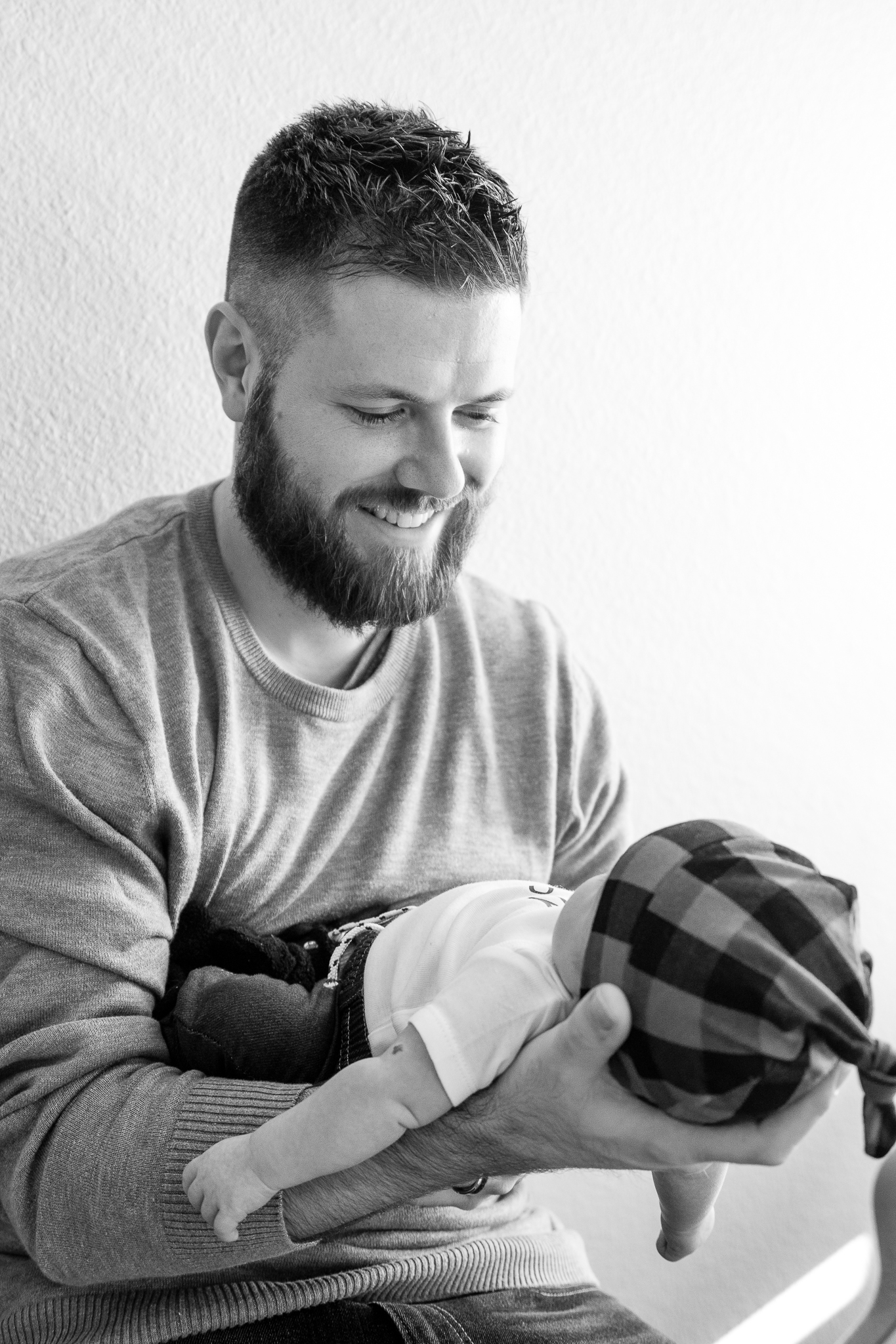 Newborn lifestyle photography of dad holding baby in black and white